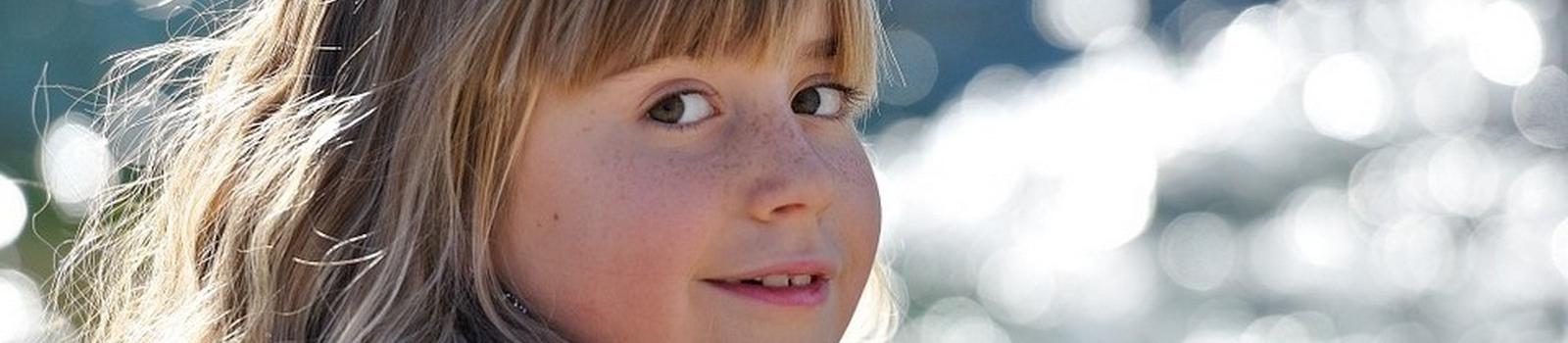 Uśmiechnięta dziewczynka na tle rozmytych odbić