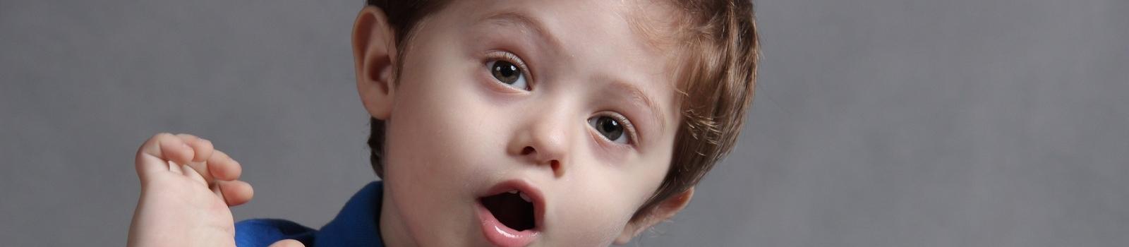 Zdziwiony chłopczyk na tle szarej ściany unosi prawą rękę